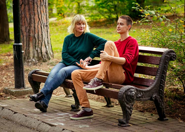 woman talking to teenage son on park bench - your teen